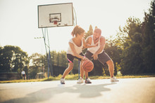 Young Happy Couple Playing Basketball Together.