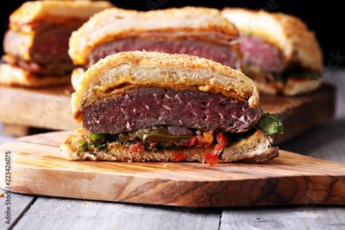 Fotografía  Cut in half angus burger on grain bun with tomato relish, lettuce and cheddar