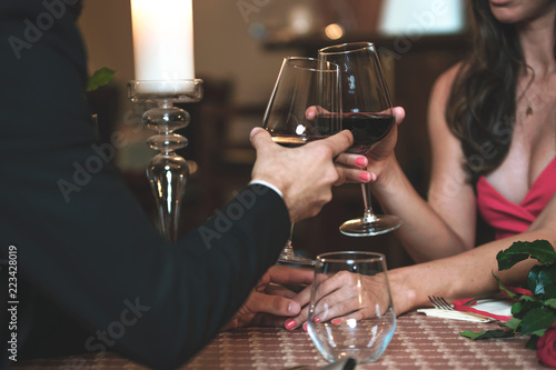 Fotografia  Couple in love holding hands and drinking wine during a romantic dinner in a restaurant ( reduced tone)