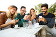 Group of four friends having fun a coffee together. Two women and two men at cafe talking laughing and enjoying their time. Using phone