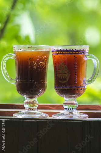 Two glass of Irish coffee on beautiful green natural background.