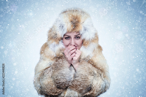 Valokuva  Frozen young woman in a fox fur coat warming hands, cold, snow, frost, blizzard