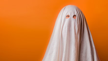 Young Child Dressed In A Ghost Costume For Halloween On Orange Background