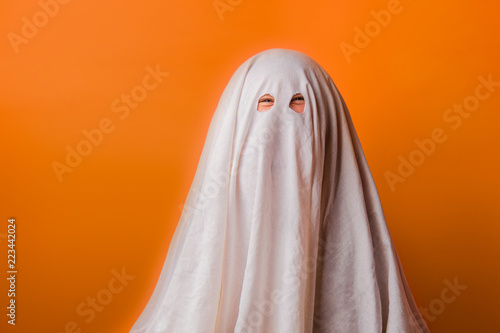 young child dressed in a ghost costume for halloween on orange background Fototapete