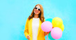 Leinwanddruck Bild - Happy beautiful smiling woman holds an air balloons in yellow coat on colorful blue background