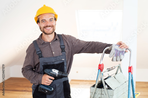 Fotografie, Obraz  Handwerker lächelnd mit Werkzeug in einem modernen Wohnraum