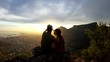 Action camera, couple sits on Cape Town mountain during sunset