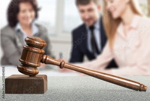 Photo Wooden judge hammer, handshake of business people on background