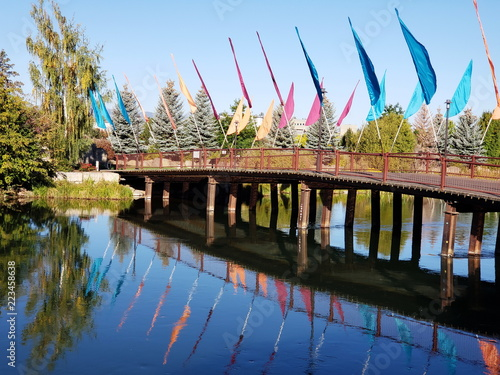 Multiple flags of a variety of brought colors in a footbridge across calm waters on the Deschutes River  that are reflecting the flags trees, and bridge Canvas Print