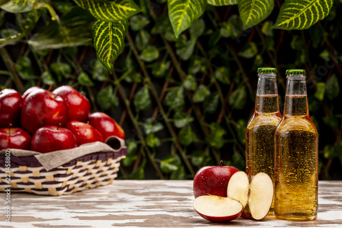 Tableau sur Toile Two bottles of nice cold cider beverage standing near braided bowl with ripe app