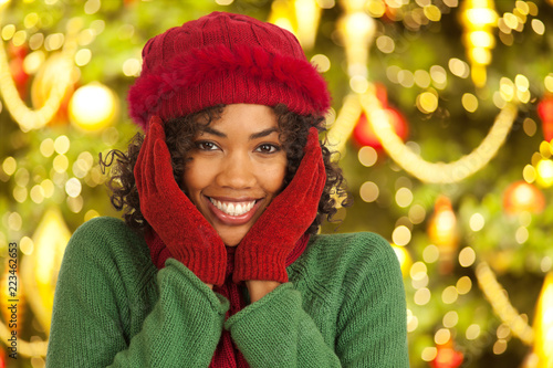 Photographie  Close up portrait of joyful young woman in front of Christmas tree