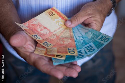 Hand holding brazilian money Fototapeta