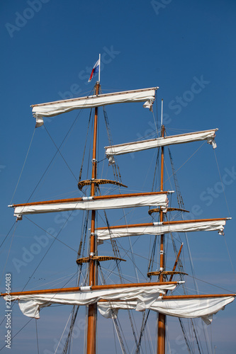 Mast, yards and sails, an old sail ship. Blue sky in background.