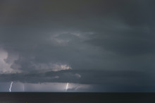 A Distant Thunderstorm Over The Ocean