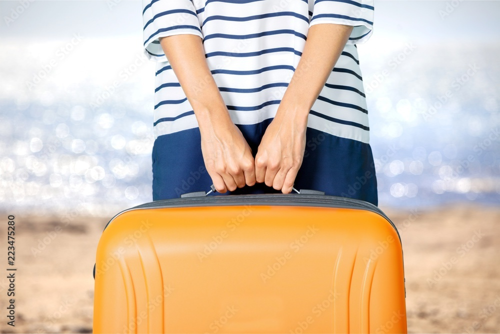 Fototapeta Woman hands holding travel suitcase