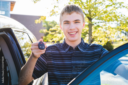 Photo Happy teenager showing off his car keys as he stands next to his car