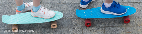 two children's skateboards, close-ups, with standing feet on them