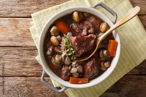 Coq au vin - french food slowly cooked cock with wine and vegetables close-up in a pot. horizontal top view from above