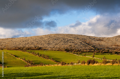 Green meadows and rocky hills. The Burren in northwestern County Clare, Ireland. Glaciated karst landscape. Landscape of Burren National Park in County Clare - Ireland