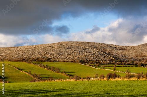 Foto op Canvas Blauwe hemel Green meadows and rocky hills. The Burren in northwestern County Clare, Ireland. Glaciated karst landscape. Landscape of Burren National Park in County Clare - Ireland