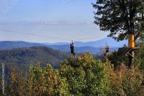 Sporty ekstremalne, mężczyzna i kobieta zjeżdżają na linie zawieszopnej nad górami
