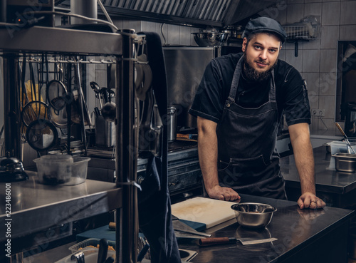 Fototapeta Bearded cook in apron and hat leaning on a table and looking at camera in kitchen. obraz