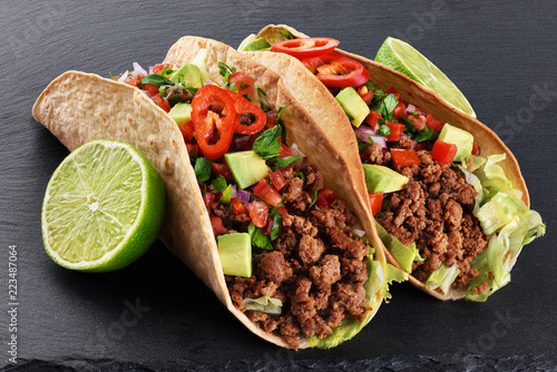 Mexican tacos with beef, tomatoes, avocado, chili and onions on a shale board background.