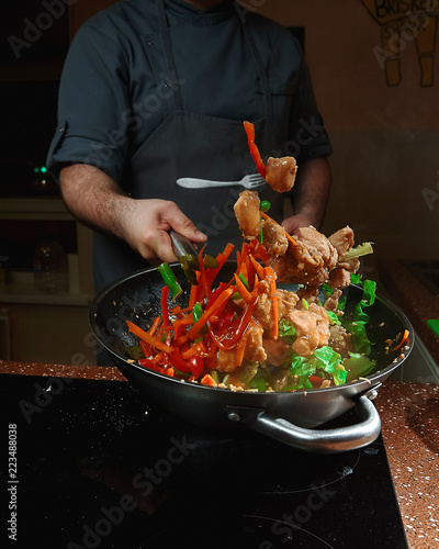 Photo  Caucasian chief cook cooking on the wok pan.Vegetables are flying