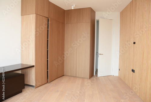 Fotografia  Wood Flooring with modern wooden wall, room door, table and wooden wardrobe