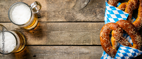 Billede på lærred Oktoberfest concept - pretzels and beer on rustic wood background, top view