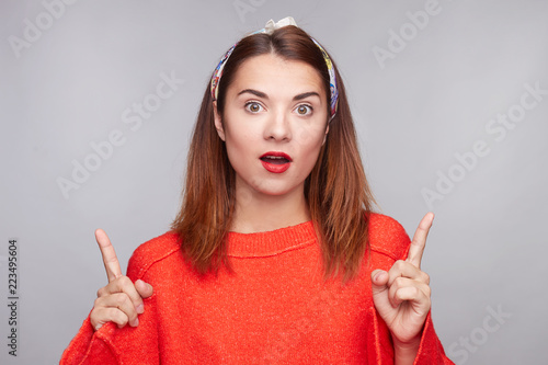 Fényképezés Studio portrait of beautiful young hipster female, stares at camera with bugged eyes, keeps jaw dropped, points with both index fingers upwards, expresses unexpectedness and shows surprise on gray