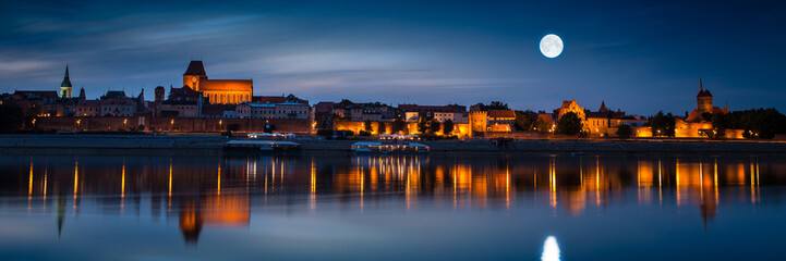 Old town reflected in river at sunset. Torun, Poland