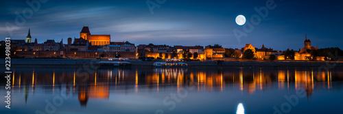 Obraz na płótnie Old town reflected in river at sunset. Torun, Poland
