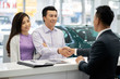 Cheerful Vietnamese couple vising car dealership in search of new vehicle
