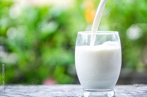 Pouring milk on drinking glass over nature sunlight morning background