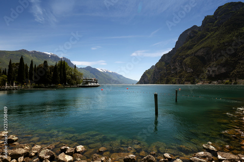 Fotobehang Oceanië Italy. Riva del Garda. View of the lake from the shore. Clear water and blue sky