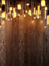 The Light From The Edison Lamp. Hang On The Background Of A Wooden Wall, Depth-of-field Camera Effects.