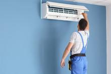 Electrician Repairing Air Conditioner Indoors
