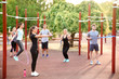 Leinwanddruck Bild - Group of sporty people training on athletic field outdoors