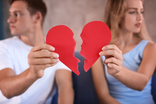 Young Couple Holding Halves Of Broken Heart On Sofa At Home. Relationship Problems