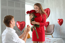 Young Man Proposing To His Beloved With Beautiful Engagement Ring At Home