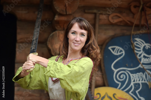 Fotografía  Woman in a green dress with a sword in hand.
