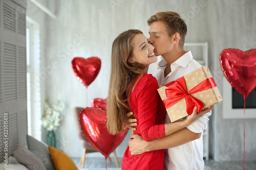 Fototapeta Young couple with gift box hugging at home obraz