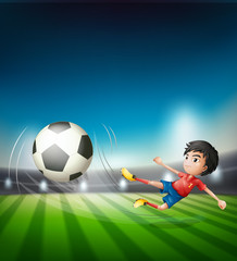 Fototapeta A football player kicking ball