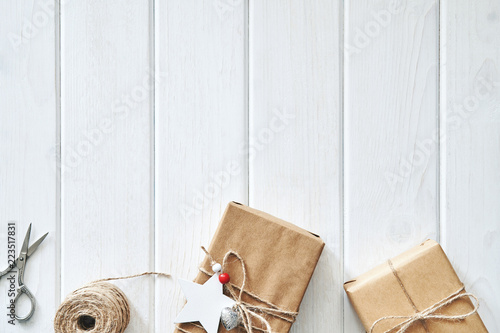 Foto op Plexiglas Retro Christmas card for your text. Decoration gift in a box of kraft paper tied with a rope with a star, a vintage scissors, christmas tree branch with a handmade rope on a background of white wooden board