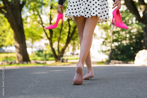 Tablou Canvas Woman holding high heel shoes in hands and walking with bare feet