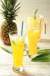 Tasty fresh cocktails with pineapple in glass on light wooden background