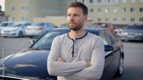 Fotografiet  pensive serious man is standing on open parking area in summer day, crossed hand