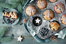 Blueberry Muffins With Sugar Icing In A Baking Tray With Christmas Decorations Around, Flat Lay
