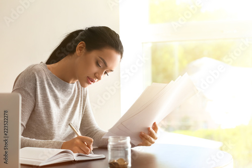 Cuadros en Lienzo  Young woman working with financial documents at table